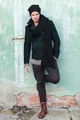 full length picture of a young fashion man posing outdoor with a foot on the wall behind him and a h