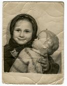 MOSCOW, USSR - CIRCA 1940s : An antique photo shows a little girl and a doll in her hands.