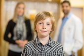 Portrait of confident boy with optometrist and mother in background at store