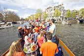 AMSTERDAM, HOLLAND - APRIL 30, 2013: Amsterdam canals full of boats and people in orange during the