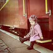 Little cute girl ready to vacation on railway station, baby girl fashion model go on travels, toned
