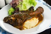 picture of lamb shanks  - Braised lamb shank with mashed potato and salad served on white plate - JPG
