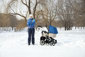 Young mother with baby stroller for a newborn in winter park