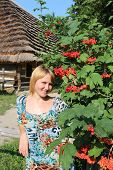 girl with red guelder-rose besides an rural house