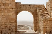 Ancient stone arch and wall with desert view during sandstorm