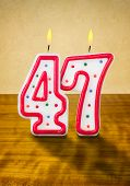Burning birthday candles number 47 on a wooden background