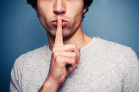 picture of hush  - Young Man Gesturing Hush With Finger On Lips - JPG