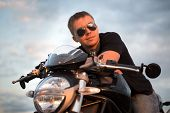 Romantic portrait handsome biker man in sun glasses sits on a bike