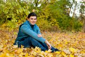Young smiling man relaxing in autumn park sitting on a folliage.