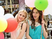 Happy romantic fashion girls with colorful balloons, outdoors. Toned.