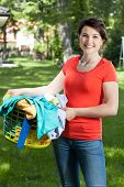 Woman Holding A Laundry Basket In Garden