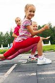 Children Training On Stadium Stretching
