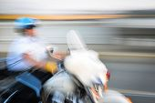 Police officer riding motorbike with motion blur effect