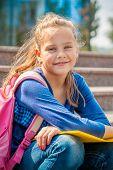 Portrait of a sweet basic school girl in the outside