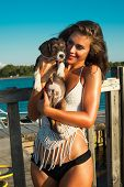smiling young woman hug little puppy, outdoor shot at seaside, sunny summer day