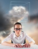 Businesswoman typing on a keyboard against blue and orange sky with clouds