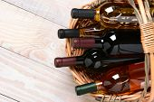 A high angle shot of wine bottles in a basket on a whitewashed wood farmhouse style kitchen table. H