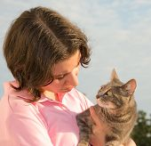 Pretty girl looking at a blue tabby cat in her arms, with the cat looking back at her