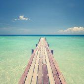 Pier wooden bridge towards sea, tropical island sea view in vintage style.