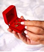 Female hand holding jewelry box with earrings.Wedding background.