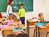Children with teacher in classroom near blackboard .