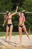 Two female athletes playing beach volleyball