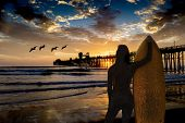 An unknown woman surfer holds her board while watching an Oceanside sunset. Oceanside is 40 miles No