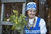 Old woman in russian ethnic clothes, outdoors.