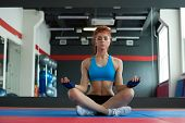 Beautiful red-haired sportswoman meditating in gym
