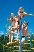 Three Cheerful Children On Bar At The Playground