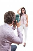 Young photographer taking photos of beautiful model with instant camera