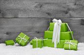 Green Christmas Presents With Snow On Grey Wooden Background For A Greeting Card Or Coupon, Voucher