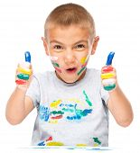 Portrait of a cute boy playing with paints and showing thumb up sign using both hands, isolated over