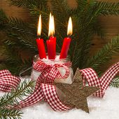 Square Christmas Card Decorated With Four Red Burning Candles, Wooden Star, Snow, Ribbon And Pine Br