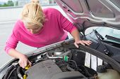 Woman inspecting broken car engine.