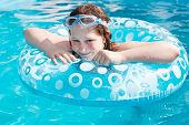 Girl On Inflatable Circle In Blue Open-air Pool