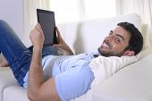 Young Happy Attractive Man Using Digital Pad Or Tablet Sitting On Couch