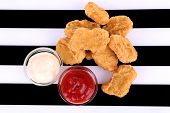 Fried chicken nuggets and sauces on striped background