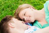 holidays, vacation, love and friendship concept - smiling couple lying on on grass in park