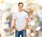 holidays, advertising and people concept - smiling young man in blank white t-shirt over sparkling b