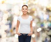 advertising, holidays and people concept - smiling young woman in blank white t-shirt over sparkling