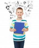 education, childhood and school concept - smiling little student boy with blue book