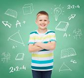 happiness, childhood, school, education and people concept - smiling little boy over green board wit