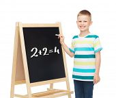 people, childhood and education concept - smiling little boy with blank blackboard over white backgr