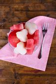 Pieces of melon and watermelon in goblet on napkin on wooden background