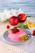Round shaped cake with fruits and berries on plate on lace napkin