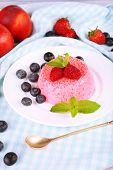 Round shaped cake with berries on plate on table cloth