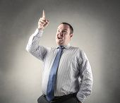 businessman pointing his fingerup and looking successful