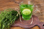 Estragon drink with lemon on cutting board on wooden background