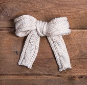 White Knitted Woolen Bow On Square Wooden Background